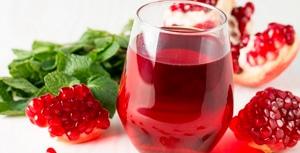 zumo de granada Granavida® en vaso con gajos de granada